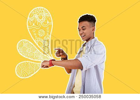 Smart Watch. Cheerful Happy Student Feeling Impressed While Using A Modern Smart Watch And Enjoying