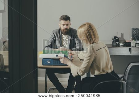 Businessman And Businesswoman Sit At Office Desk. Bearded Man And Woman Have Business Meeting. Conce