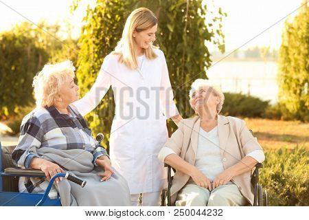 Nurse from care home walking with senior people outdoors