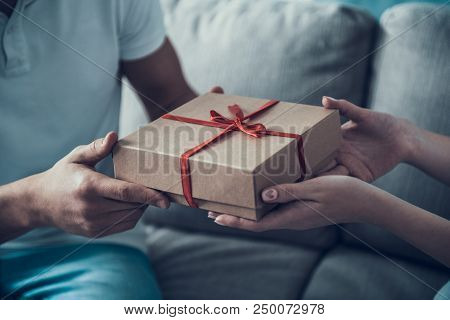 Close Up. Girlfriend Giving Gift Box To Boyfriend. Love Concept. Happy Young Couple. Holding Gift Bo