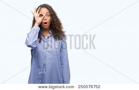 Young hispanic business woman doing ok gesture shocked with surprised face, eye looking through fingers. Unbelieving expression.