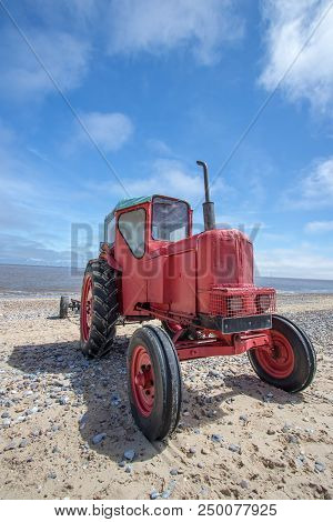 Quirky red diesel beach tractor. Vintage little red tractor on the coast against blue sky. poster