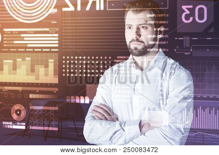 Serious Consideration. Calm Attentive Web Developer Frowning And Standing With His Arms Crossed Whil