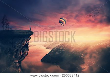 Scenery View As A Wander Girl Silhouette On The Edge Of A Cliff Watching The Beautiful Sunset Sky. E