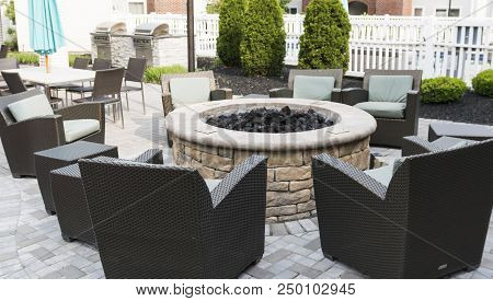 A Hotels Patio Is Set Up With A Fire Pit And Chairs With Tables And Umbrelllas And A Barbeque Grill