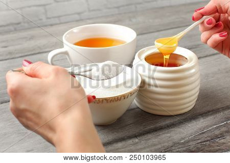 Young Woman Hands Holding Spoon Of Sugar, And Honey Deciding What To Put In Tea. Refined Vs Natural