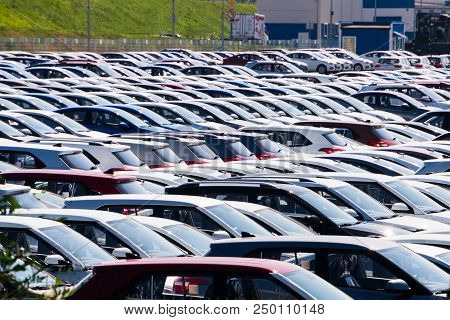 Storage Parking Lot Of New Unsold Cars. Cars Of Different Classes And Colors Are In The Parking Lot.