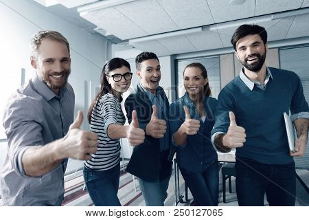 Only Positive Emotions. Cheerful Smiling Young Colleagues Standing In The Office And Thumbing Up Whi