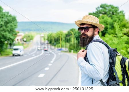 Man at edge of highway wait transport. Travel alone. Hitchhiking means transportation gained asking strangers for ride in their car. Hitchhiker travel alone try stop transport to get to destination. poster