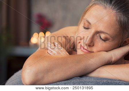 Closeup face of mature woman lying on a massage table with eyes closed in a wellness center. Blonde woman lying on front and relaxing after beauty massage. Serene senior woman in a spa salon.