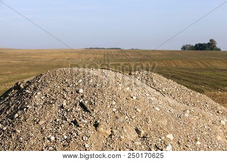 A Pile Of Sand And Rubble Piled Near The Agricultural Field During The Road Works And Repairs