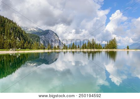 Ehrwalder Almsee - Beautiful Mountain Lake In The Alps, Tyrol, Austria. Sky Reflects In The Clean Wa