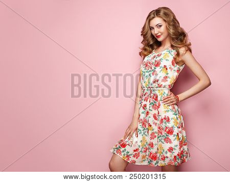 Blonde Young Woman In Floral Spring Summer Dress. Girl Posing On A Pink Background. Summer Floral Ou
