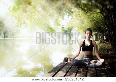 Young Women Meditate While Doing Yoga In Atmosphere Peaceful.