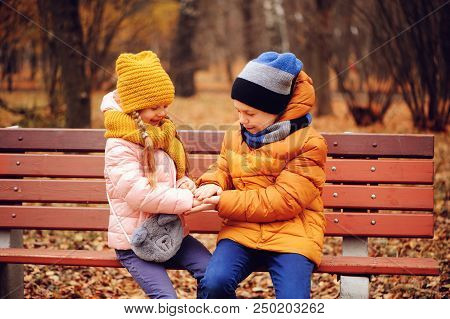 Autumn Portrait Of Happy Kids, Brother And Sister Sitting On Bench In Park And Hugs
