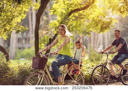 Happy Family Is Riding Bikes Outdoors And Smiling- Little Boy On Bike With Mother And Father