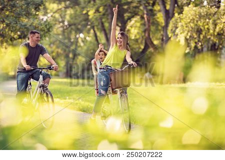 Family Sport And Healthy Lifestyle. Happy Active Father And Mother With Kid On Bicycles Having Fun I