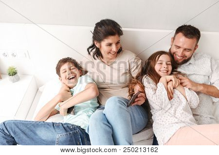 Portrait from above of caucasian family with two children laughing and lying together on bed in apartment