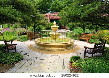 Courtyard Including A Water Fountain Surrounding Chairs Besides Manicured Plants And Trees Taken In