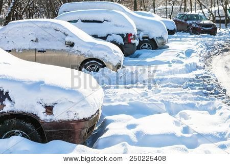 Snow-covered Cars On Car Parking In Moscow City In Sunny Winter Day