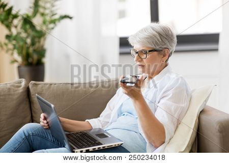technology, old age and people concept - happy senior woman in glasses with laptop computer and smartphone using voice command recorder at home