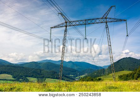 Power Lines Tower On A Meadow Against The Blue Sky. Lovely Energy Industry Background. Efficient Ele