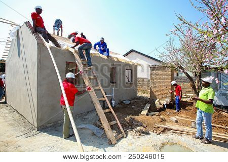 Diverse Community Members Building A Low Cost House In Soweto
