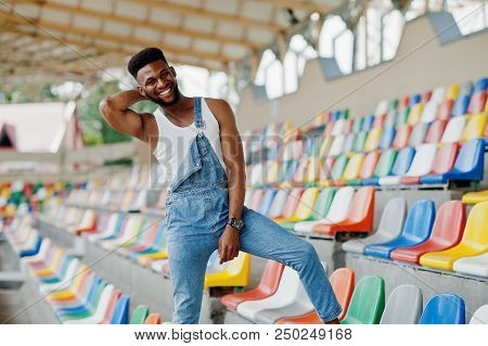 Handsome African American Man At Jeans Overalls Posed On Colored Chairs At Stadium. Fashionable Blac