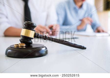 Close Up Of Judge Gavel And Two Golden Marriage Ring, Contract Decree Of Divorce (dissolution Or Can