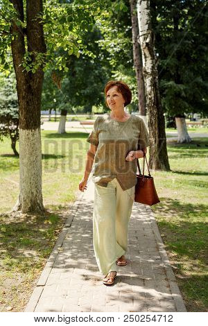 A Woman Aged Vigorously Walks Along A Path In A Park Dressed In Linen Clothes And With Flying Hair