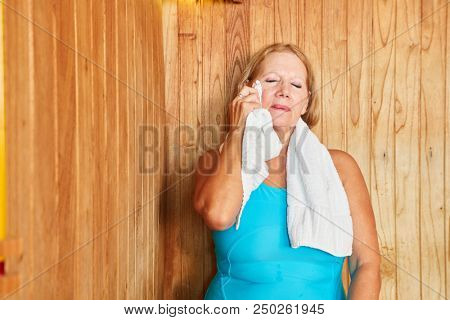 Senior woman sweats in the steam sauna and wipes the sweat off