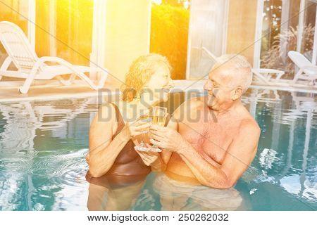Senioren Paar beim Sekt trinken im Hotel Pool beim Wellness Urlaub