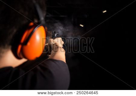 Man Shooting Pistol Gun, Fire Bullet, And Wear Orange Ear Cover In Shooting Range