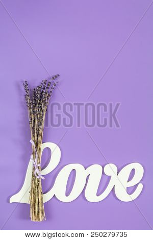 White Letters Forming Word Love Written With Beautiful Dried Lavender Bouquet On Violet Surface