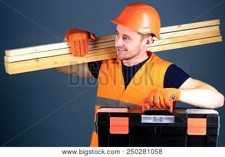 Professional Woodworker Concept. Man In Helmet, Hard Hat Holds Toolbox And Wooden Beams, Grey Backgr
