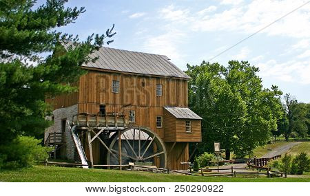 Trees Frame A Brown Restored Gristmill And Waterwheel