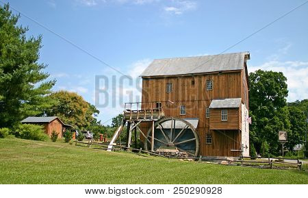 A Brown Restored Grist Mill And Waterwheel