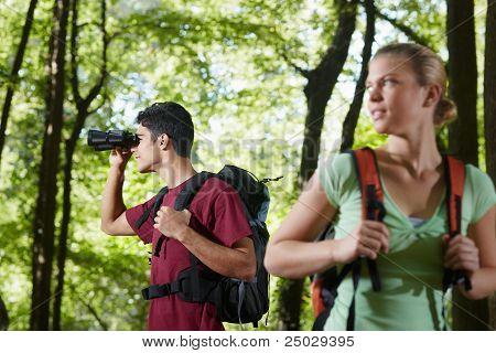 Joven y mujer Senderismo en el bosque con binoculares
