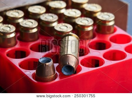 A Partially Full Red Box Of 40 Caliber Hollow Point Bullets With Several Empty Slots And One Bullet