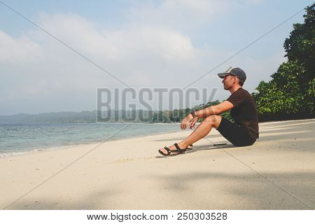 A Young Guy Sits On A White Sandy Beach And Looks At The Sea On An Exotic Island. Man Enjoying On Em