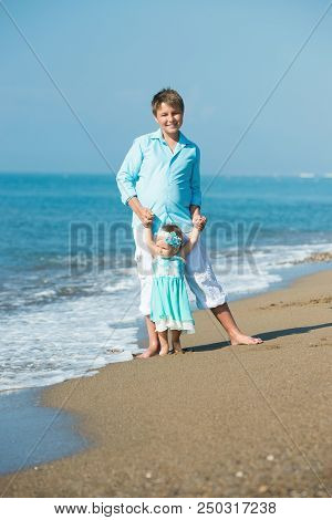 The Elder Brother Walks With His Younger Sister On The Beach. Walking On The Beach To See The Waves