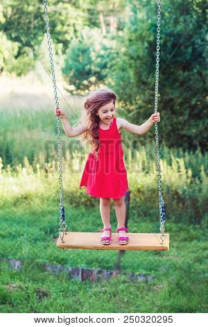 Beautiful Little Girl Is Sianding And Smiling  On Swing At Summer Day, Happy Childhood Concept