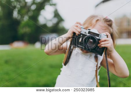 Little Cute Child Baby Girl In Light Dress Take Picture On Retro Vintage Photo Camera On Green Grass