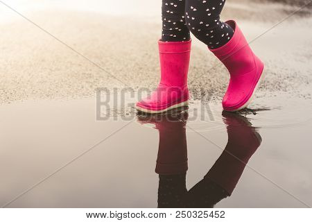 Feet Of Child In Pink Rubber Boots Jumping And Splashing Over Puddle After Rain.