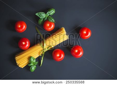 Raw Spaghetti Pasta With Fresh Tomatoes And Basil Leaves On Dark Background. Top View, Copy Space.
