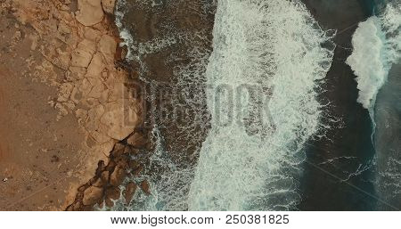 Aerial Photography. The Sea Wave Covered The Stone Shore. On The Sea Rose Strong Waves.