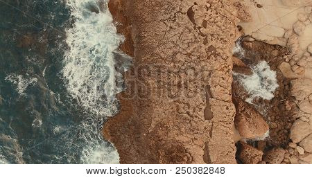Aerial Photography.stone Cliff. Waves Beat Against The Rocks. Foam Waves. One Wave Rolls On The Othe