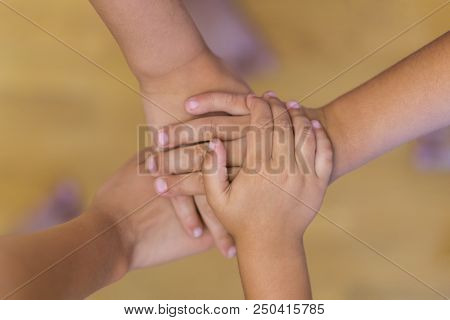 The Concept Of Child Friendship And Mutual Assistance. Children's Hands Stacked To Unity. Children's