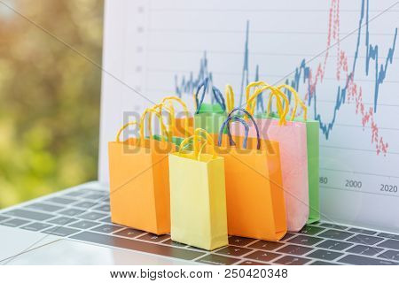 Many Colourful Paper Bags On Laptop Keyboard With Chart Background. Consumers Can Buy Products Direc