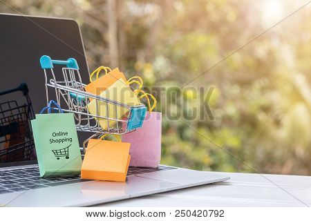 Colorful Paper Bags Are In Trolley On Laptop Keyboard. Consumers Can Buy Products Directly  From A S
